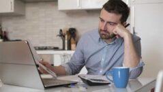 Muž si sjednává u PC dlouhodobou půjčku